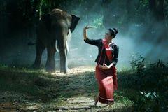 O estilo do nordeste da mulher tailandesa nova bonita ? apreciar dan?ar e jogar com o elefante na selva fotografia de stock