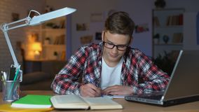 O estudante adolescente diligente nos vidros termina trabalhos de casa e olha diretamente à câmera video estoque