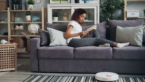O estudante afro-americano bonito está girando no livro robótico do hoover e de leitura que aprecia o passatempo e que relaxa no  vídeos de arquivo