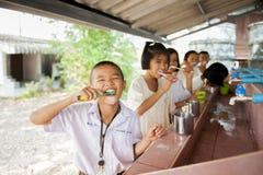 O estudante aprende escovar os dentes imagem de stock