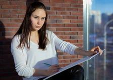 O estudante bonito escreve com lápis coloridos imagem de stock royalty free