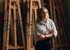 O estudante bonito novo da arte ou da arquitetura da menina está sonhando de seu futuro no fundo de madeira velho das armações Imagem de Stock