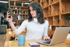 O estudante bonito novo do blogger da menina com cabelo encaracolado longo em uma camiseta branca e com os fones de ouvido no pes imagem de stock royalty free