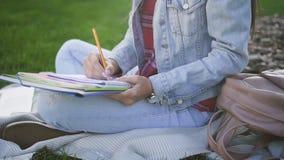 O estudante bonito novo está escrevendo leituras no caderno vídeos de arquivo