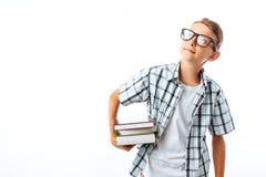 O estudante bonito que guarda uma pilha de livros, um botânico vai com livros estudar no estúdio em um fundo branco foto de stock