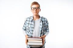 O estudante bonito que guarda uma pilha de livros, um botânico vai com livros estudar no estúdio em um fundo branco imagem de stock