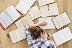 O estudante cai adormecido ao estudar fotografia de stock