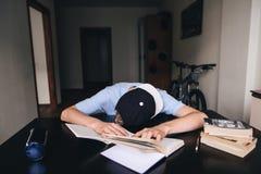 O estudante caiu trabalhos de casa fazendo adormecidos em livros e em cadernos em sua sala Ensino em casa Sono na tabela Fotos de Stock Royalty Free