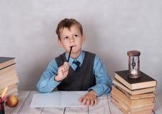 O estudante da escola pensa sobre a solução de uma tarefa na matemática Fotos de Stock Royalty Free