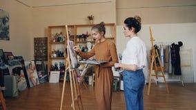 O estudante de arte delgado da jovem mulher está pintando o funcionamento na imagem e está falando a seu professor amigável que e filme