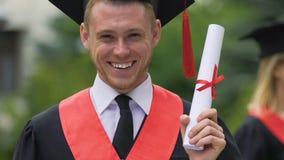 O estudante de graduação feliz e orgulhoso que guarda o ensino superior certificate à disposição vídeos de arquivo