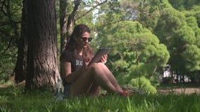 O estudante de jovem mulher usa a tabuleta digital no parque video estoque