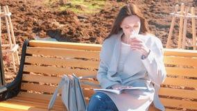 O estudante de mulher moreno bonito novo senta-se no banco no parque da mola, lê-se um livro e bebe-se o café filme