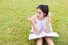 O estudante de mulheres que senta-se na grama e no Livro Branco no joelho Sua mão que guarda o lápis imagens de stock royalty free