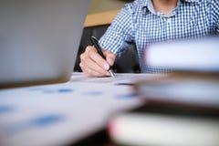 O estudante do homem redige a informação da tabuleta portátil quando prepar foto de stock royalty free