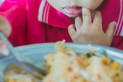 O estudante do jardim de infância está comendo a almofada tailandesa fotografia de stock
