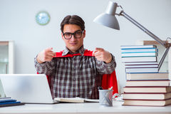 O estudante do super-herói com livros que estuda para exames Fotos de Stock