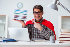 O estudante do super-herói com livros que estuda para exames Imagens de Stock Royalty Free