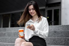 O estudante encantador do divertimento em uma camisa branca senta-se na rua imagens de stock