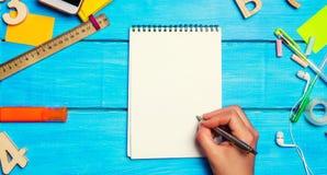 O estudante escreve a pena em um caderno Vista superior Configura??o lisa fontes de escola na mesa da escola, artigos de papelari fotos de stock