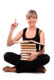 O estudante está sentando-se com a pilha de livro imagem de stock