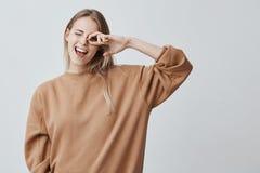 O estudante fêmea alegre com cabelo reto louro, exulta os exames com sucesso passados, contentes de ter a reunião com Foto de Stock