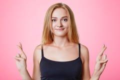 O estudante fêmea bonito novo mantém os dedos cruzados, faz o desejo desejado, acredita-o no sucesso ou na boa sorte, isolado sob Foto de Stock
