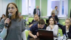 O estudante fêmea bonito novo na sala de aula está apresentando seu projeto da graduação com os auxílios visuais à audiência filme