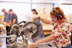 O estudante fêmea In Carpentry Class que usa a circular viu fotos de stock