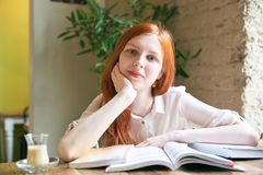 O estudante fêmea da menina atrativa nova com pele branca e cabelo vermelho longo é livros de leitura, estudando, cercado por liv imagens de stock