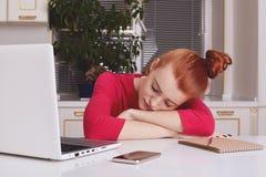 O estudante fêmea do gengibre cansado da fadiga trabalha toda a noite no papel do curso, cai adormecido diretamente no lugar de f imagens de stock
