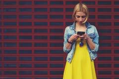 O estudante fêmea do moderno no vestido que usa o telefone celular para conecta ao rádio fotos de stock