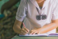 O estudante fêmea escreve um caderno para graduados no schoo secundário fotografia de stock