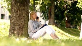 O estudante fêmea fala pelo telefone e escreve um diário no parque Escrit?rio do ambiente natural Benef?cios do ar livre do traba video estoque