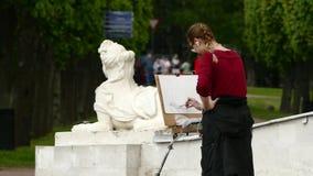 O estudante fêmea impressionante de escola de arte veio ao ar livre no parque e aprende tirar video estoque