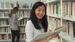 O estudante fêmea lê o livro na biblioteca fotos de stock