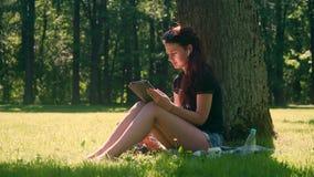O estudante fêmea no parque usa a tabuleta digital no parque vídeos de arquivo