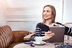 O estudante fêmea novo conversar na tabuleta digital com amigo ao sentar-se no café, mulher atrativa que usa a almofada quando Foto de Stock Royalty Free