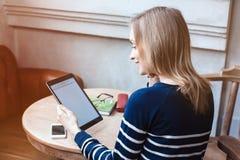 O estudante fêmea novo está apreciando o tempo livre, quando se sentar com a almofada de toque na cafetaria interna A mulher boni Imagens de Stock Royalty Free