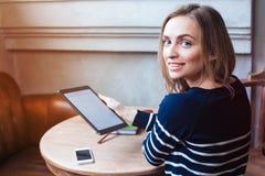 O estudante fêmea novo está apreciando o tempo livre, quando se sentar com a almofada de toque na cafetaria interna A mulher boni Fotografia de Stock