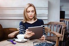 O estudante fêmea novo está conversando na tabuleta digital com amigo ao sentar-se no café, mulher atrativa que usa o portátil Fotografia de Stock Royalty Free