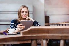 O estudante fêmea novo está conversando na tabuleta digital com amigo ao sentar-se no café, smilling a utilização atrativa da mul Imagem de Stock Royalty Free