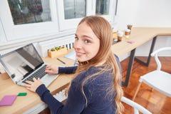 O estudante fêmea novo está datilografando no PC do portátil fotografia de stock royalty free