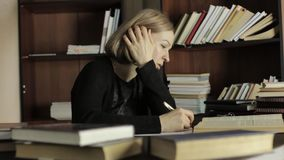O estudante fêmea que senta-se na mesa e redige para fora a informação necessária do livro vídeos de arquivo