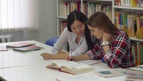 O estudante fêmea senta-se para baixo perto de seu colega na biblioteca vídeos de arquivo