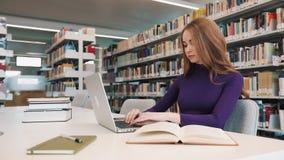 O estudante fêmea trabalha com livros e um portátil que senta-se na tabela na biblioteca video estoque