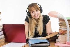 O estudante feliz com os fones de ouvido que preparam-se para exames na tabela olhou o quadro Foto de Stock