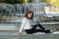 O estudante l? o livro na fonte imagem de stock royalty free