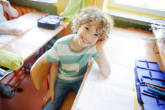 O estudante louro da escola senta-se na mesa em uma classe fotografia de stock