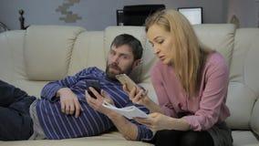 O estudante louro lê suas notas, e seu noivo que senta-se no sofá e nos smartphones dos usos vídeos de arquivo